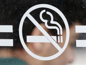 A student waits for a bus behind a no-smoking sign at the State University of New York at Albany.