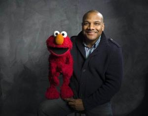 In this Jan. 24, 2011 file photo, Elmo puppeteer Kevin Clash poses with the Sesame Street muppet in the Fender Music Lodge during the 2011 Sundance Film Festival in Park City, Utah.