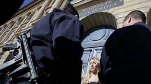 A Femen activist is surrounded by French police officers during a  demonstration in Paris.
