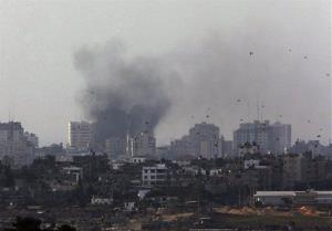 Birds fly as a plume of smoke is seen over central Gaza Strip, after an airstrike by Israeli forces, as seen from the Israel Gaza border, Monday, Nov. 19, 2012.