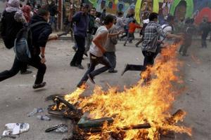 Egyptian protesters run past a bonfire during clashes with security forces, unseen, in Cairo, Egypt, Wednesday, Nov. 21, 2012.