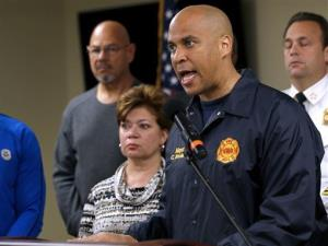 In this Oct. 29, 2012, file photo, Newark Mayor Cory Booker, right, speaks during a news conference at the Office of Emergency Management in Newark.