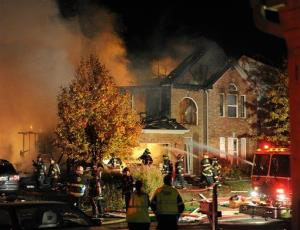 Authorities say a loud explosion has leveled a home in Indianapolis and set four others ablaze in a neighborhood, causing several injuries.
