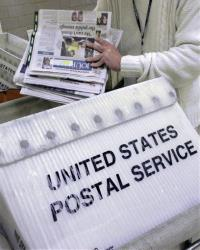 In this Dec. 5, 2011 file photo mail is loaded into bins for transport at the Capitol Station, in Springfield, Ill.