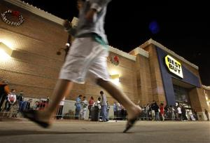 Shoppers stand in line outside a Best Buy department store as another rushes to join in before the store's opening at midnight for a Black Friday sale Thursday, Nov. 22, 2012, in Arlington, Texas.