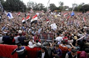 Supporters of Mohamed Morsi chant slogans and wave his campaign posters outside the Presidential palace in Cairo, Egypt, Friday, Nov. 23, 2012.
