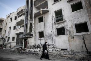 In this Saturday, Nov. 17, 2012 photo, a Syrian woman walks in front of a destroyed hospital where heavy clashes took place, on the outskirts of Aleppo, Syria.