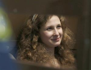In this Wednesday, Oct. 10, 2012 file photo, Maria Alekhina sits in a glass cage at a courtroom in Moscow.