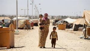 A Syrian refugee woman walks with her children at the Zaatari refugee camp in Mafraq, Jordan.