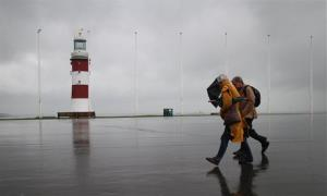 Two people walk along the Hoe, in Plymouth, England, in heavy rain and high winds Saturday, Nov. 24, 2012.
