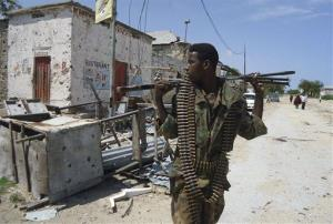 A Somali government soldier looks over at a closed restaurant as he patrols in Bakara Market junction in Mogadishu, Somalia Sunday, Aug. 21, 2011.
