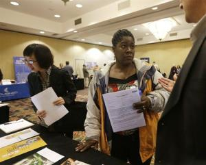 In this Thursday, Oct. 25, 2012, photo, Angela Winters of Schenectady, NY, center, talks to a recruiter during a job fair at the Marriott Hotel on, in Colonie, NY.