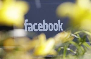 This Friday, May 18, 2012, file photo shows Facebook's headquarters behind flowers in Menlo Park, Calif.