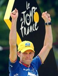 This 2003 file photo shows Lance Armstrong waving on the podium after he won his fifth consecutive Tour de France cycling race, in Paris.