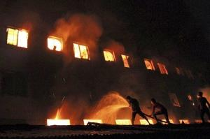 Bangladeshis and firefighters battle a fire at a garment factory in the Savar neighborhood in Dhaka, Bangladesh, late Saturday, Nov. 24, 2012.