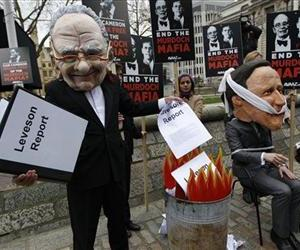 A campaigner wearing a giant mask depicting Rupert Murdoch pantomimes burning the Leveson report while another wearing a mask depicting David Cameron, sits tied to a chair during a protest, Nov. 29, 2012.