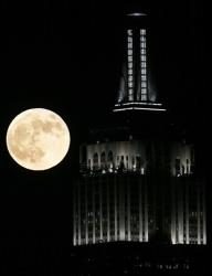 A full moon rises near the Empire State Building, as seen from Hoboken, N.J., Wednesday, Nov. 28, 2012.