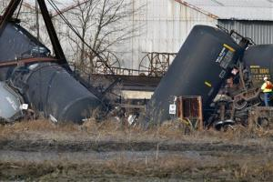 An official stands by derailed freight train tank cars in Paulsboro, NJ, this morning.
