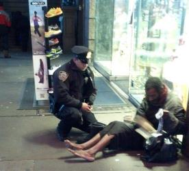 This photo provided by Jennifer Foster shows New York City Police Officer Larry DePrimo presenting a barefoot homeless man in New York's Time Square with boots Nov. 14, 2012.
