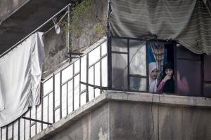 Syrian women watch a demonstration after Friday prayers in the Bustan Al-Qasr district of Aleppo, Syria.