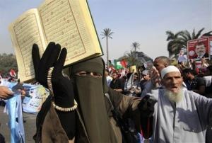 A supporter of Egyptian President Mohammed Morsi holds a Quran and a poster of the president at a rally in front of Cairo University in Cairo, Egypt, Saturday, Dec. 1, 2012.