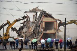A house in the middle of a new road is torn down on the outskirts of Wenling city, in eastern China's Zhejiang province, Saturday, Dec. 1, 2012.