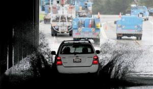 A vehicle transits a flooded underpass in San Rafael, Calif., on Sunday, Dec. 2, 2012, as utility workers work to repair a downed power line.