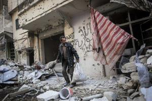 In this Sunday, Dec. 2, 2012 photo, a man collects his belongings after his home was damaged due to heavy fighting between Free Syrian Army fighters and government forces in Aleppo, Syria.