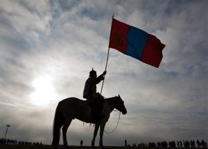 A Mongolian horseman holds a national flag in Khui Doloon Khudag, on the outskirts of Ulan Bator, Mongolia, Thursday, July 12, 2012.