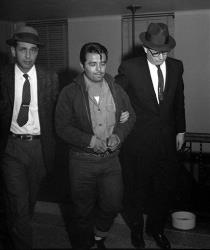 In this Jan. 6, 1960 file photo, Perry Edward Smith is led by police officers into the courthouse at Garden City, Kan.