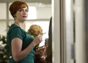 In this image released by AMC, Joan Harris, portrayed by Christina Hendricks, celebrates a promotion in a scene from Mad Men.