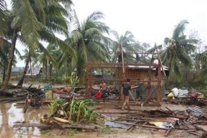 Residents repair their damaged homes after Typhoon Bopha made landfall in Compostela Valley province yesterday.