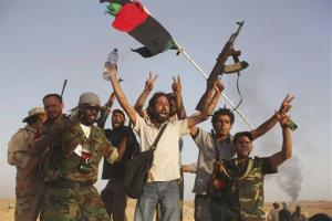 In this Sept. 18, 2011 file photo, former rebel fighters celebrate as smoke rises from Bani Walid, Libya. A new report shows the US knew Islamic radicals were getting weapons from Qatar and the UAE.