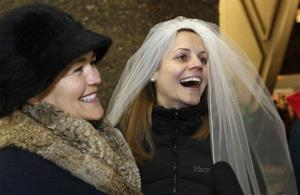Amy Andrews, right, smiles as she wears a veil while standing in line with her partner, Jeri Andrews, Wednesday, Dec. 5, 2012, in Seattle.