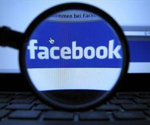 A magnifying glass is posed over a monitor displaying a Facebook page.