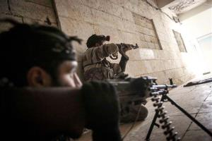 In this Wednesday, Dec. 5, 2012 photo, Free Syrian Army fighters aim their weapons at the entrance of a building during heavy clashes with government forces in Aleppo, Syria.