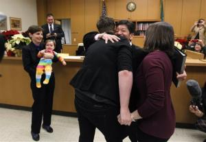 Judge Mary Yu embraces Emily Cofer, right, and Sarah Cofer after declaring them wed moments after midnight in the in the King County Courthouse, Sunday, Dec. 9, 2012, in Seattle.