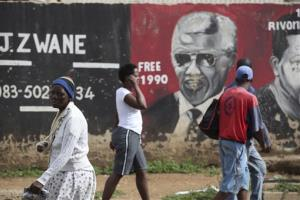 People walk past a mural of Nelson Mandela in the Soweto area of Johannesburg, Sunday, Dec. 9, 2012. South Africa's presidency says that Mandela, 94, was admitted to a hospital Saturday.