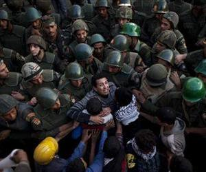 Egyptian protesters push army soldiers standing guard in front of the presidential palace in Cairo, Egypt, Dec. 9, 2012.