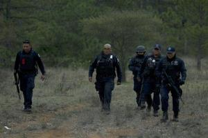 Federal police officers return from the crash site near Iturbide, Mexico.