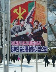 North Koreans make their way past a poster with the slogan  Advance toward the final victory in Pyongyang yesterday.