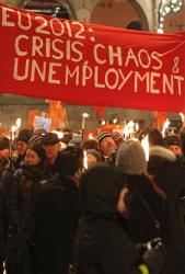 People walk with torches to protest against the awarding of the Peace Prize to the EU bloc, in Oslo, Norway, Sunday Dec. 9, 2012.