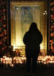 Jenny Guerrero pays tribute to Jenni Rivera at a makeshift memorial in front of an image of the Virgin of Guadalupe at the Plaza Mexico shopping center in Lynwood, Calif., early Monday, Dec. 10, 2012.