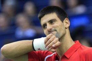 Novak Djokovic of Serbia wipes his face in the men's singles semifinal match at the Shanghai Masters tennis tournament in Shanghai, China, Saturday Oct. 13, 2012.