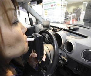 A staff of Tokyo-based electronic alcohol detector maker demonstrates a new drunken driving deterrence device.