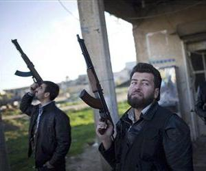 Free Syrian Army fighters look at a Syrian Army jet, not pictured, in Fafeen village, north of Aleppo province, Syria, Tuesday, Dec. 11, 2012.