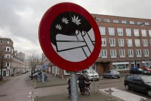 Mothers and their children leave a nearby school as a sign prohibiting the use of marijuana in a designated area is seen in Amsterdam, Wednesday Dec. 12, 2012.