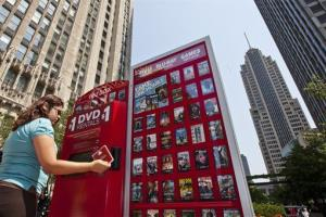 In this photo taken by AP Images for Redbox, Noemi Tejeda rents a movie from a pop up Redbox Kiosk at Pioneer Court on Michigan Avenue in Chicago, on Wednesday, Aug. 24, 2011.