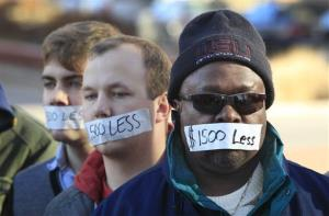 Protesters hold a silent protest in Lansing, Mich., Wednesday over the state's new right-to-work law.