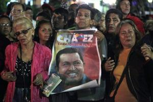 People, one holding an image of Venezuela's President Hugo Chavez, gather to pray for him at Simon Bolivar square in Caracas, Venezuela, Tuesday, Dec. 11, 2012.